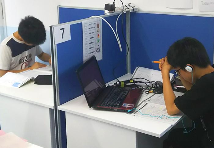 机に向かって勉強する子供