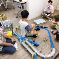 室内でプラレール遊びをする子供たち